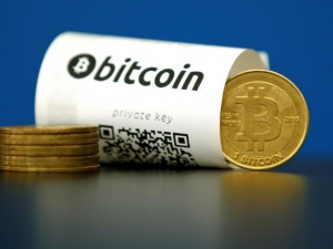 Some commentators say Bitcoin's creator could help resolve a row among the currency's software developers.